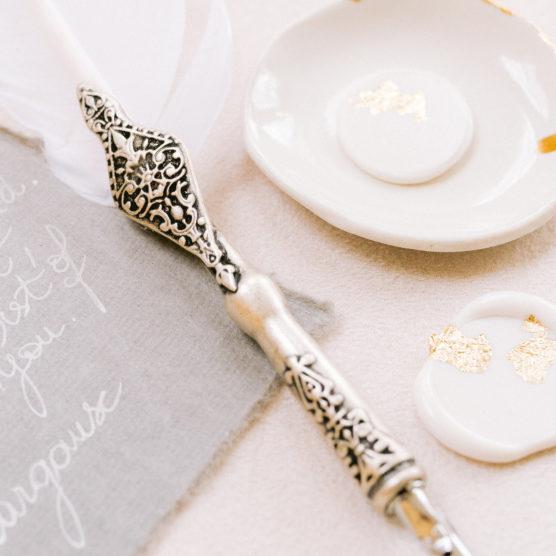 Flatlays plume et de sceau de cire blanc et or mis en scène par la wedding planner Amélie Pichon Weddings