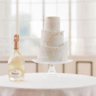 Wedding Cake sur table avec une bouteille de champagne Ruinart mis en scène par la wedding planner Amélie Pichon Weddings