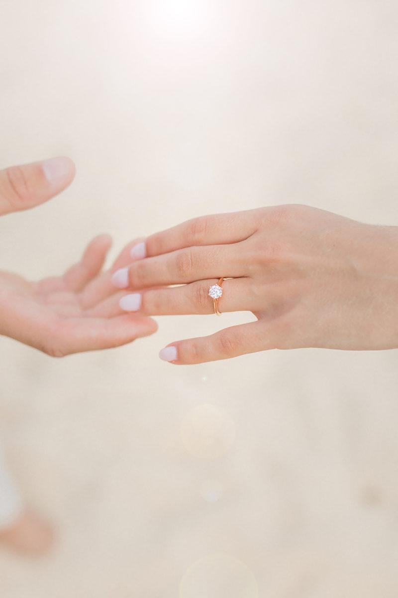 Deux mains de couple se tenant montrant la bague de fiançaille mis en scène par la wedding planner Amélie Pichon Weddings