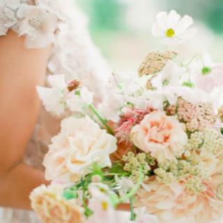 Bras d'une mariée portant son bouquet de fleurs mis en scène par la wedding planner Amélie Pichon Weddings