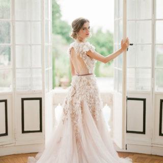 Mariée regardant vers nous devant une grande fenêtre mis en scène par la wedding planner Amélie Pichon Weddings