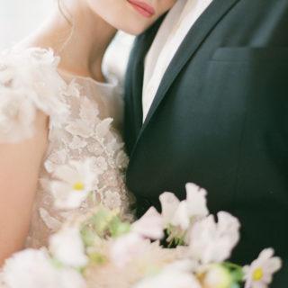 Couple de mariés en costume et robe avec des fleurs mis en scène par la wedding planner Amélie Pichon Weddings